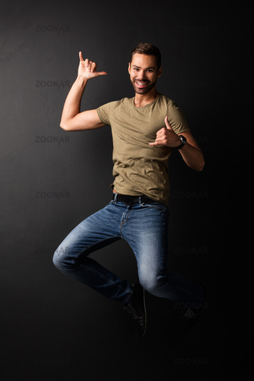 Happy handsome young man jumping and dancing
