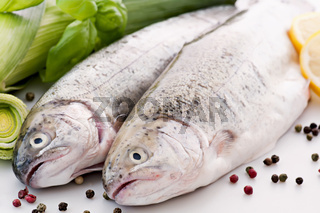 Two fresh rainbow trout with leek as closeup on white background