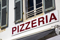Pizzeria signage in red letters on white board