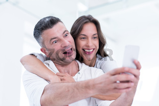happy couple using mobile phone at home