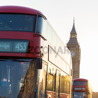 Red double-decker buses passing on Westminster Bridge in London, UK.
