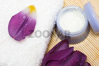 Spa essentials (cream, white towel and violet flower)