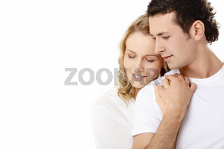 The young couple embraces on a white background