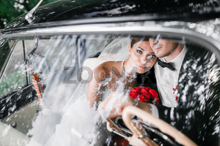 The bride and groom behind the wheel of retro car. Wedding.