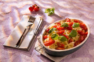 Italian Farfalle pasta with tomatoes and basil over a colored background