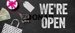 Shopping concept - We are open written on a blackboard
