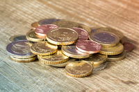 Euro coins piled on wooden table