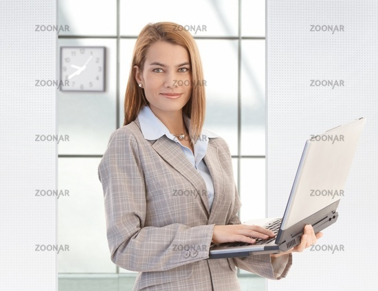 Attractive businesswoman holding laptop smiling