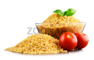 Bowl of uncooked bulgur isolated on white.