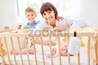 Mutter und Sohn gemeinsam am Babybett