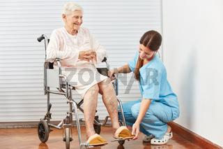 Pflegekraft hilft behinderter Frau im Rollstuhl