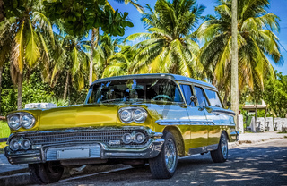 HDR - Goldener amerikanischer Oldtimer parkt unter blauem Himmel und Palmen in Varadero Kuba