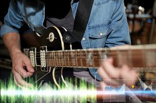 close up of musician playing guitar at studio