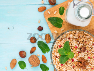 Muesli, milk and nuts on blue background