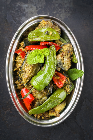 Indian Vegetable Curry Fry with Eggplant and Sweet Peppers as close-up in a Korai