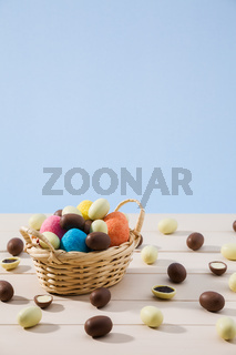 Easter chocolate eggs in a small basket with blue background