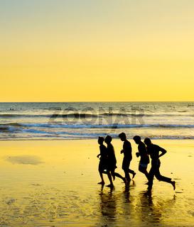 People running ocean beach, Bali