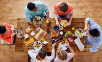 people with smartphones eating food at table