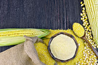 Flour and grits corn with bag on wooden board