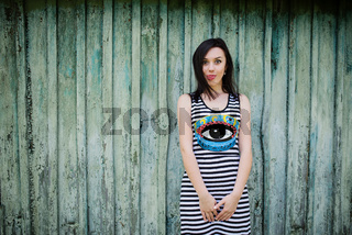 Brunette model girl at dress with stripes showing tongue background cian wooden background.
