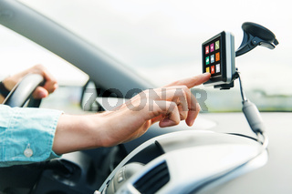 close up of man with icons on gadget driving car