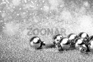 Silver christmas balls on shining glitter background