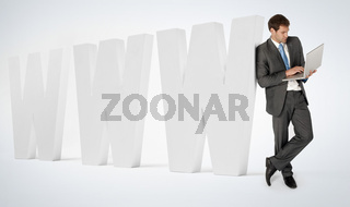 A businessman on a laptop leaning against www wording.