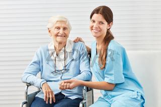 Fürsorgliche Pflegekraft und Seniorin im Rollstuhl