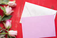 Message card on envelope and roses