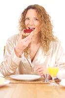 Junge Frau beisst in Marmeladenbrötchen