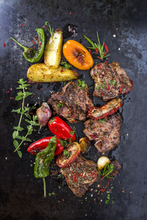 Barbecue T-bone lamb steak with Vegetable and seasonings as top view on a rusty metal sheet
