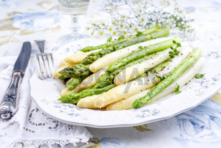 Boiled green and white Asparagus as top view on a plate