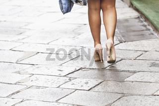 Eine Frau mit Rock geht mit hohen Schuhen über eine gepflasterte Straße.
