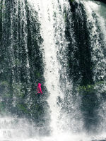 Feamale hiker, tourist, model standing or walking under the Sgwd Yr Eira Waterfall in Wales. In Portrait framing.