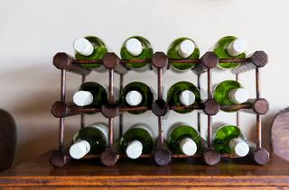 white wine bottles stored on wooden rack