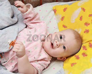 A smiling baby in bed with a dummy in a hand