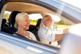 happy senior couple driving in car