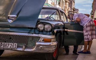 Cuban mechanic fixing oldtimer after breakdown