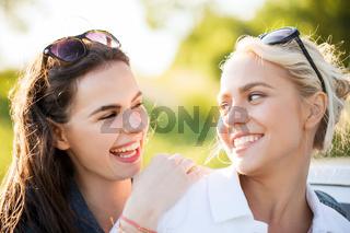 happy women or teenage girls laughing outdoors