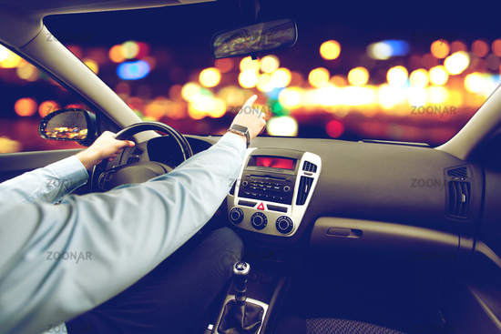 close up of man driving car and pointing finger