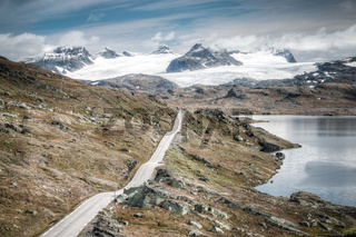 Vintage retro effect filtered hipster style travel image of mountain road leading to spectacular glaciers and lakes.