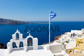 View on calm sea surface through traditional Greek white church arch