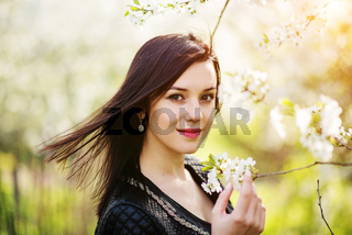 Close up portrait of young brunette girl with cherry blossom at spring garden.