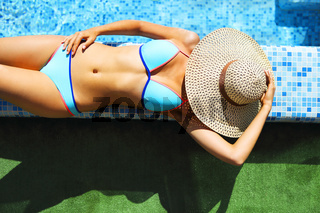 Woman in straw hat relaxing by the pool