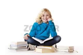 Schulmädchen sitzt am Boden und lernt aus Büchern