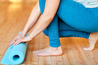 close up of woman rolling yoga mat at gym
