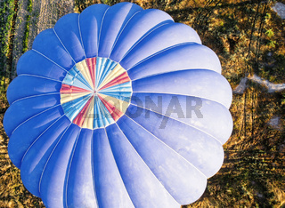 View from above onto a blue balloon shortly before landing in Cappadocia, Anatolia, Turkey, from the hot-air balloon