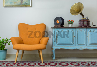Retro orange armchair, vintage wooden light blue sideboard, old phonograph (gramophone), vinyl records on background of beige wall, tiled porcelain floor, and red carpet