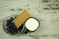 Cup of milk and crisp bread with cranberries