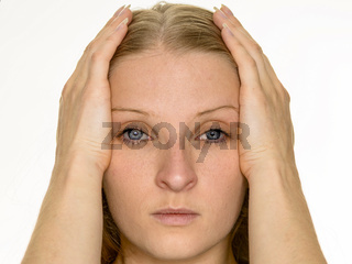 Junge blonde Frau hält Ihren Kopf zwischen den Händen gestützt.